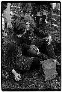 Hippie couple smoking and sitting on grass