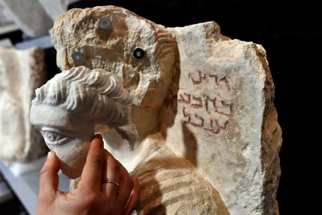 A restorer fixes a restored piece of the face of a bust, which is one of the two funeral reliefs from Palmyra archeological site that will be restored at the Higher Institute of Conservation and Restoration (ISCR - Istituto Superiore per la Conservazione ed il Restauro) in Rome, on February 16, 2017. The busts of a man and a woman, dated from the 2nd and 3rd century AD and destroyed by the Islamic State group (IS), have been entrusted to the care of the technical and restorers of the ISCR in Rome. By the end of this month, they will be returned to their place of origin. Alberto PIZZOLI / AFP