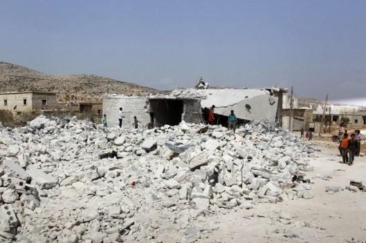 Становници сиријске провинције Идлиб (северозапад, уз границу са Турском) посматрају зграду уништену 24. септембра бомбардовањем из ваздуха. САД и њихови арапски савезници отворили су нови фронт у борби са милитантима Исламске Државе Сирије и Ирака (ИСИС) (Амар Абдула/Ројтерс)