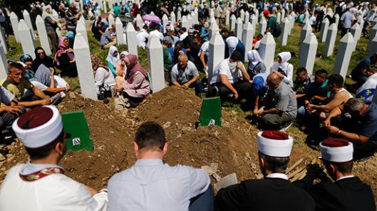 People sit around graves and tombstones at the Memorial Center Potocari, near Srebrenica, Bosnia and Herzegovina July 11, 2015 (Reuters / Antonio Bronic)