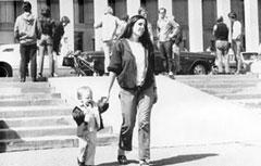 Фрида (као 2 године стара) са Розмери Мекгвајер испред Речног улаза у Пентагон 1976. године Фридина мама, Лиз МекАлистер и брат Џери (у колицима) се виде у позадини