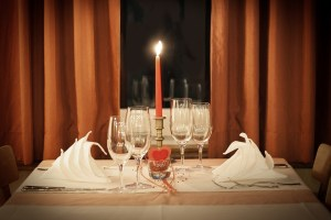 Table setup with a red candle at the center for Valentine's dinner