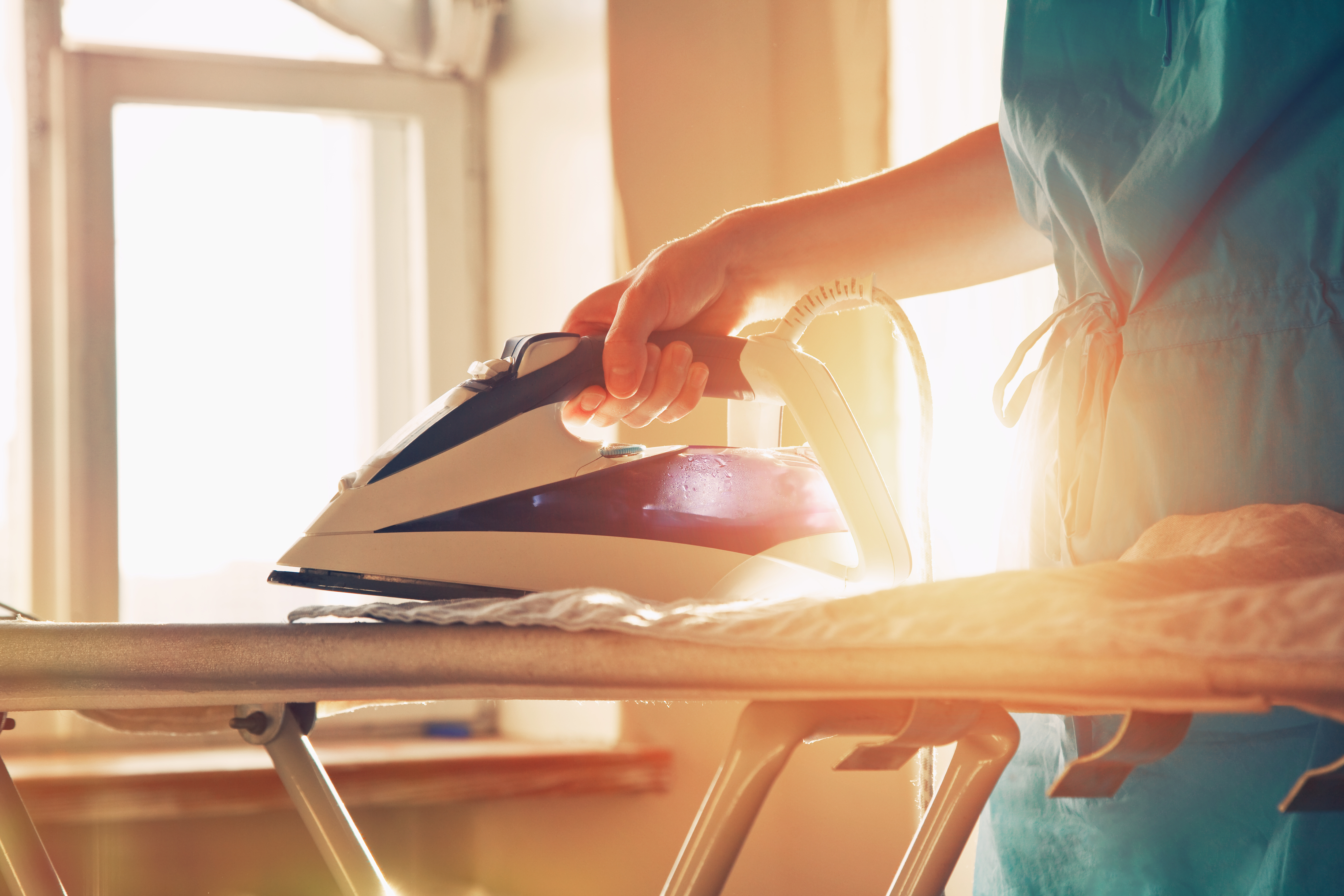 A person ironing clothes on a board
