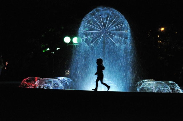 little girl playing by the fountain