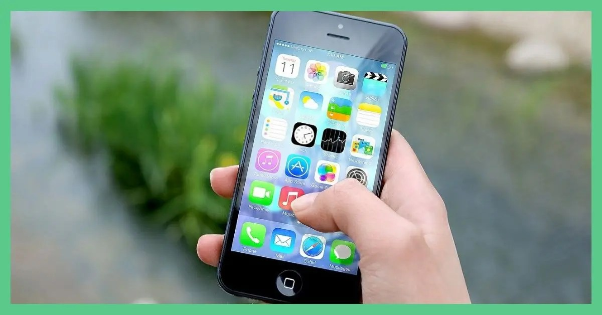The image shows a hand holding an Apple iPhone. The screen is switched on and you can see different apps on the screen. There's some grass and gravel in the background of the image. The picture has a green border. It's being use as the feature image for 'SIM only vs contract phone: is the saving worth it?'