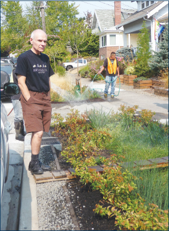 The Green Streets rain garden on Northeast 45th Avenue has space for people to step from cars, notes resident Tom Thomas, left. The plantings help manage runoff from heavy rains. Contractor Jermarino Romero, right, waters a new garden in hot weather. The city is seeking volunteer stewards to care for the green spaces. (Janet Goetze)