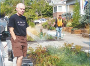 The Green Streets rain garden on Northeast 45th Avenue has space for people to step from cars, notes resident Tom Thomas, left. The plantings help manage runoff from heavy rains. (Janet Goetze)