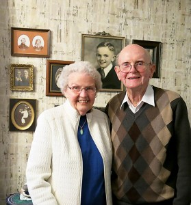 Carol and Art Wahlers, the first president of Concordia's Neighborhood Association in the mid-1950s, stand in the dining room of their Concordia home in front of a photo gallery of their ancestors. Married for 60 years, the Wahlers have four children; Mark, the oldest son, is the current provost of Concordia University.
