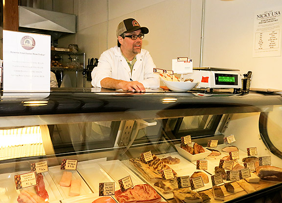 Standing behind the meat case at Tails and Trotters, chief trotter and co-owner Mark Cockcroft is ready to take customer's orders.