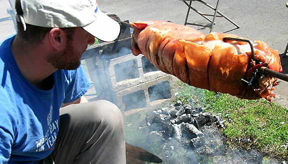 Zeph Shepard roasted a pig to the delight of passers-by who eventually accepted his invitation to partake of free beverages and food. (Phill Colombo)