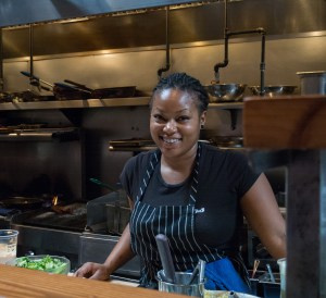 Antoinette Williams prepares to dress a salad for lunch at Tasty N Sons where customers can view kitchen chaos while sitting on stools at the counter.