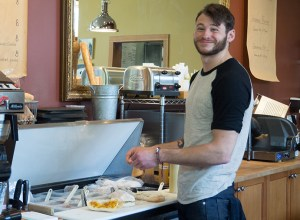 Brian Wasilewski makes sandwiches to order at Foster & Dobbs located on Northeast 15th Avenue. In addition to wine and chocolates, the cafe offers cheese boards as well as soups and salads for dining in or take-out.