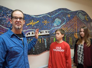Portland artist-in-residence Mark Brody worked with Beverly Cleary eighth-grade students Beth Emer and Rowan Hamilton to create a mosaic of the Tilikum Crossing Bridge, which hangs in the entryway to the Fernwood campus school.