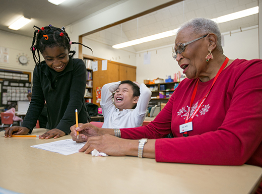 AARP Experience Corps mentor Betty Jones helps young students with their reading at Prescott Elementary School. (Metropolitan Family Service)