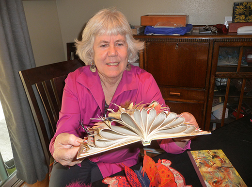 Marilyn Stablein created an artist's book by altering a conventional book with bowed pages where butterflies and flowers alight.  Interest in artists' books has been growing since the 1960s. (Janet Goetze)