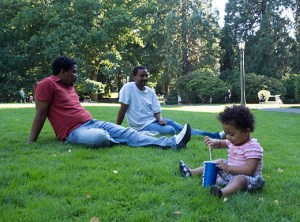 Meklit, an enthusiastic 18-month-old girl, enjoys an outing at Laurelhurst Park with (left to right): family friend Abdeg and her father, Getachew sitting on the lawn on a sunny Sunday afternoon.