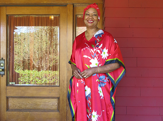 Carolyn Brown, long-time Piedmont neighborhood resident, welcomes friends and customers to her Arts and Crafts style home built in 1906. She's wearing a bright red caftan from her Elegance and More collection, which she sells by appointment in her home.