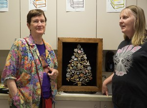 Rose Center instructor Annemarie Wright. left, discusses supplies and strategies for making a jeweled holiday tree with participant Sheryl Wolfington. Wright bought some of the pieces from Albertina's Jewel Box and scoured thrift stores for velvet dresses and skirts to use as material for the board. (Judy Nelson)