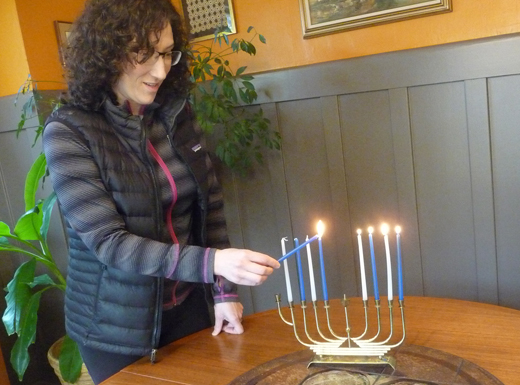 "Sherry uses a small menorah to show the correct order for lighting eight candles on successive nights to remember the miracle of Chanukah, or ""dedication,"" when only one undefiled cruse of oil lasted for eight days. The event followed a Jewish victory over an army intent on forcing a Greek lifestyle on Jewish inhabitants in Israel. (Janet Goetze)"