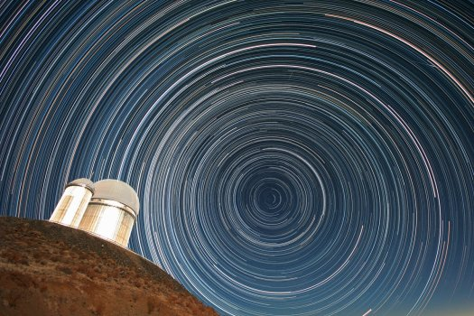 Can you find the North Star in this image? It is the star that is closest to the middle of the concentric rings of star trails. This is a long exposure photograph of real stars as seen over the course of several hours during the night.