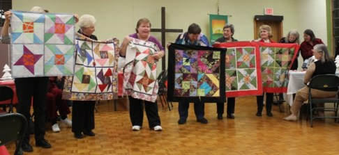 Mystery quilts from November 2016 class conducted by Barbara Badger. From left to right: Kristin Farwig (unfinished, held by Cathy Russell), Judy McWhorter, Barbara Badger, Susan Kraterfield, Anne Ware and Chris Epperley.