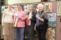 Challenge Quilt winners Judy McWhorter, Judy Coffman and Susan Kraterfield display their ribbons. Donna Kittleson organized the challenge and created the theme.
