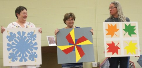Left to Right: Susan Kraterfield, Loretta Bedia and Denise Lloyd with their Barn Quilts. Made in a Starry Eyed Quilters Workshop.