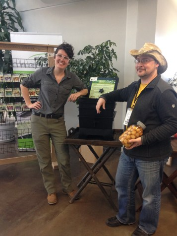 Fulbright Scholar Starr Brainard and ReThink Red Deer Project Lead Rene Michalak pose at the EcoLiving registration near a worm compost tower and heirloom seeds for sale
