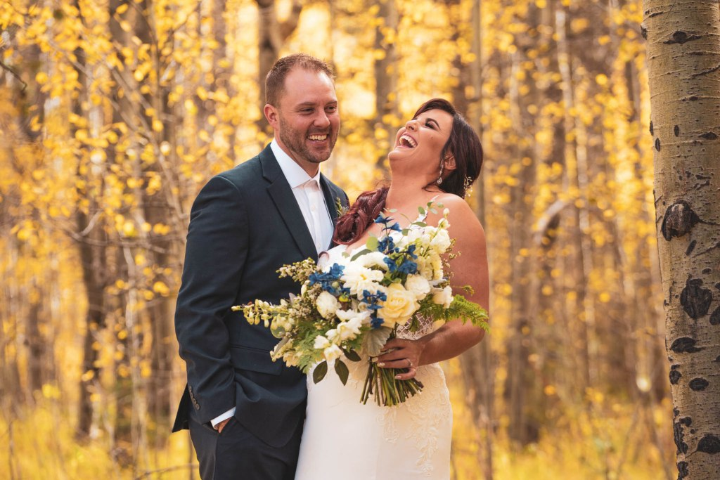 Bride and groom laughing in an aspen forest during their wedding portraits at South Lake Tahoe