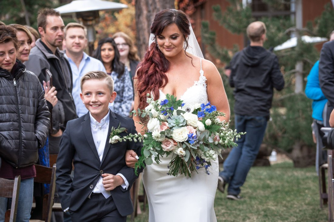 Bride walking down the aisle holding hands with her young son