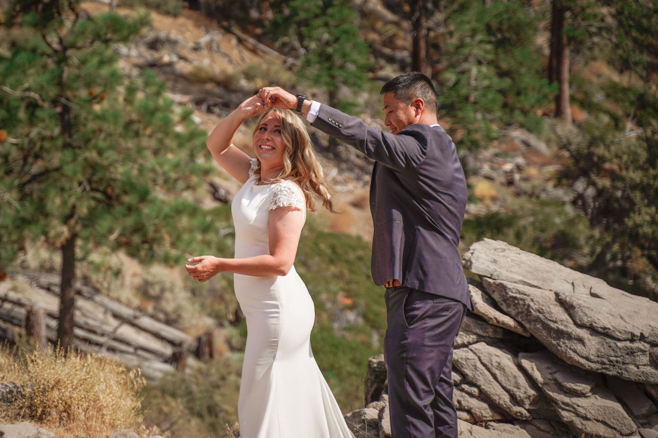 Bride and groom dancing during their first look at Cave Rock, South Lake Tahoe