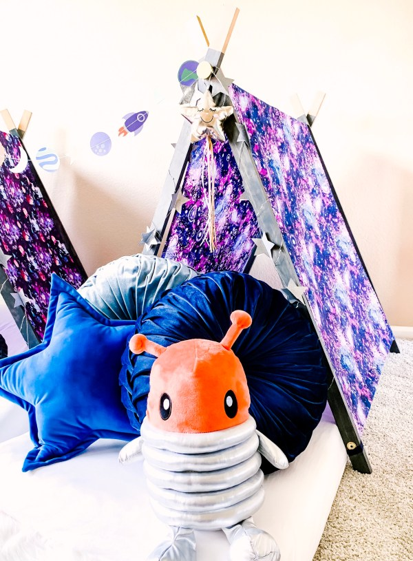Small tent for children's sleepover with Galaxy themed tent cover, blue pillows and orange alien stuffed toy.