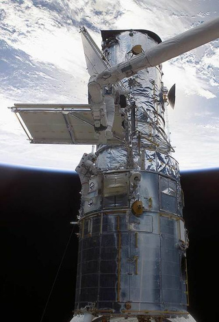 John Grunsfeld @SciAstro Making repairs on the Hubble Space Telescopr.