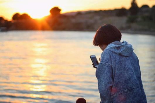 海辺でスマートフォンを構える人