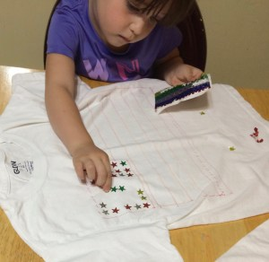 Make this July 4th flag shirt with your kids. Toddlers, preschoolers, and kids of all ages will enjoy this fun project. It's easy even for someone not crafty!
