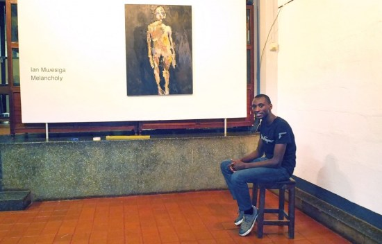 The artist, Ian Mwesiga sits in front of his painting, I am only Human