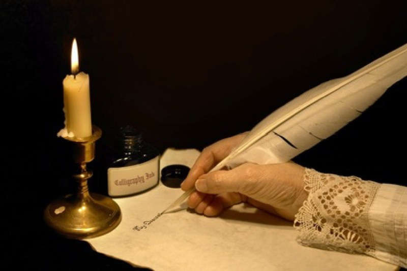 Female hand writing on a parchment with a quill