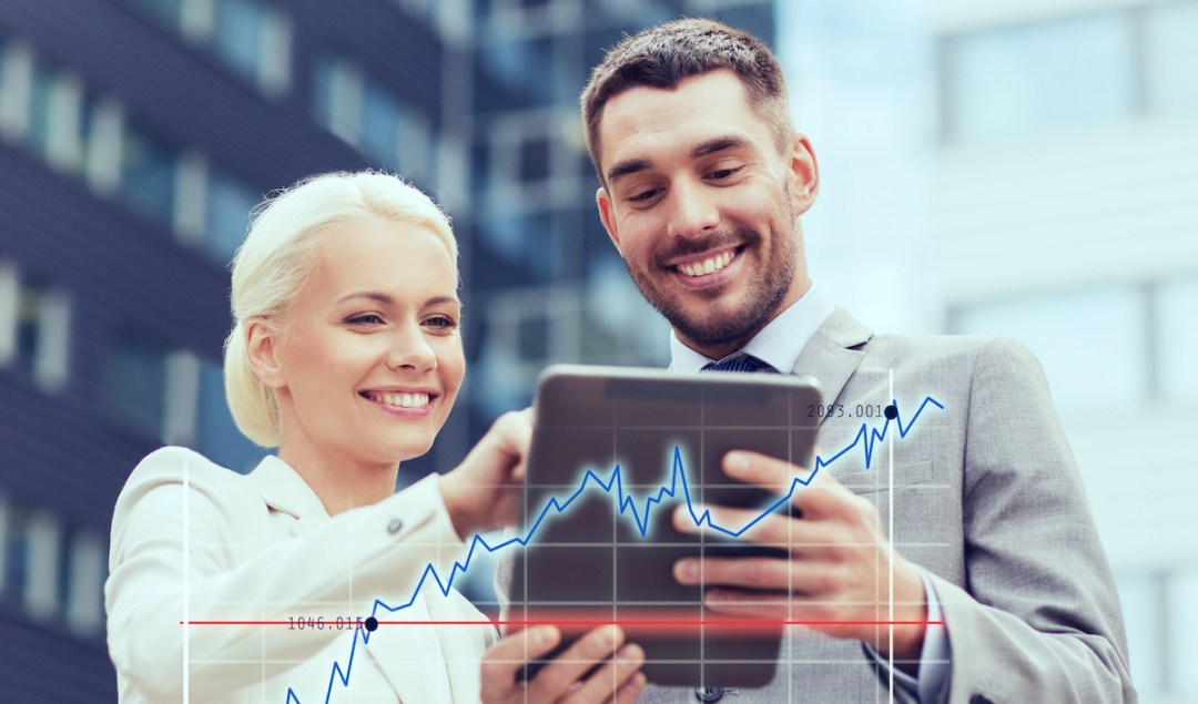 Smiling business man and woman reading sales data on tablet.