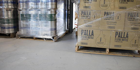 kegs and growlers on pallets atop polyurethane floor