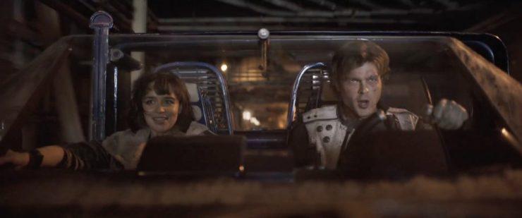 """We horen Han Solo zeggen """"I have running scams on the street since I was ten"""". Waarna we de speeder die we eerder al zagen door de straten van een onbekende stad zien scheuren. Deze keer krijgen we wel een goed beeld van de inzittenden. En zoals verwacht zijn het inderdaad Han Solo (Alden Ehrenreich) en Qi'Ra (Emilia Clarke)."""