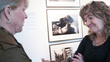 """April Saul, right, award-winning photojournalist, chats with a show visitor during her one-night photo exhibit, """"Camden, N.J. - A City Invincible,"""" March 20 in Camden."""