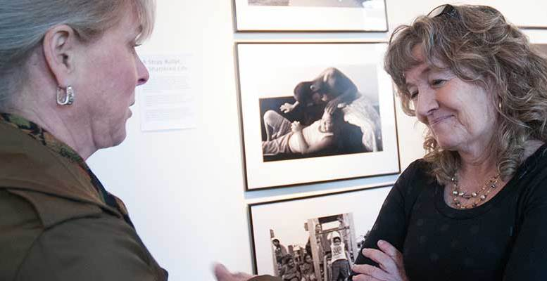 "April Saul, right, award-winning photojournalist, chats with a show visitor during her one-night photo exhibit, ""Camden, N.J. - A City Invincible,"" March 20 in Camden."