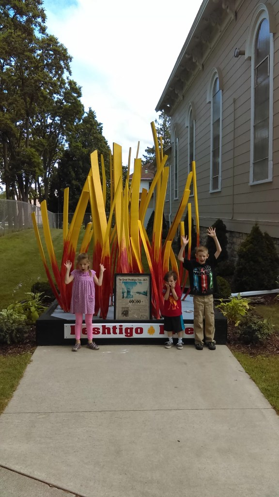 Kids in front of a museum sign that looks like a fire
