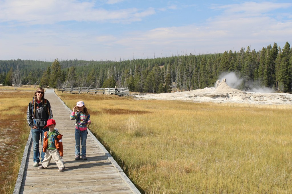 A family on a board walk in Yellowstone, without huge crowds around.