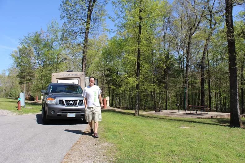 Man in front of travel trailer smiling at nice campsite