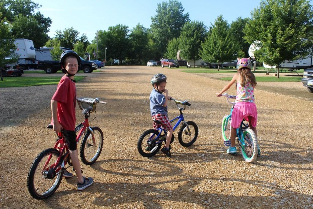 Three kids on bikes in an RV park