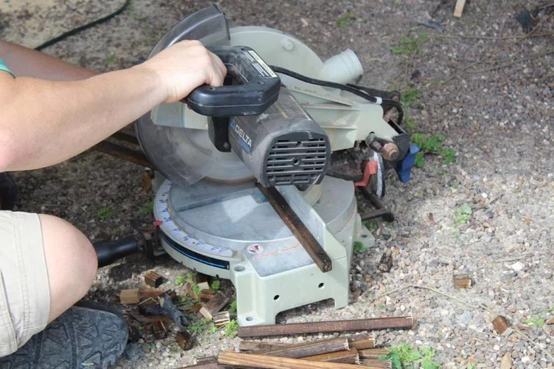 Man using chop saw to cut square stock
