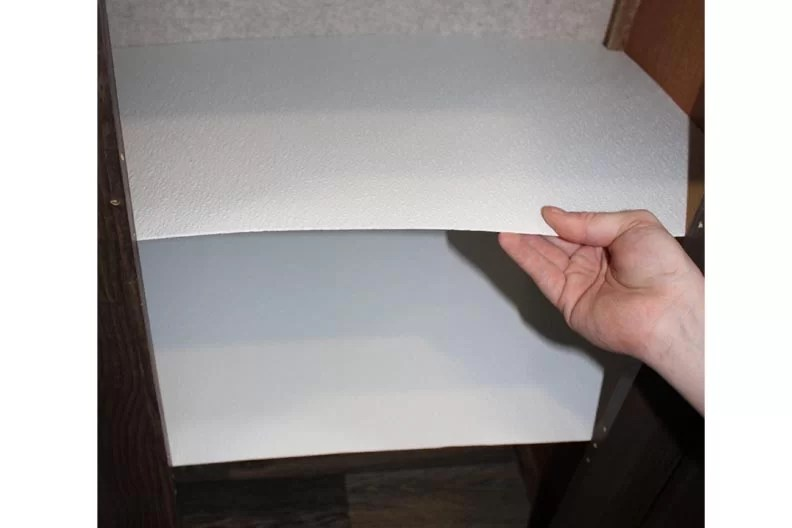 Hand holding cut fiberglass panel where shelf will be