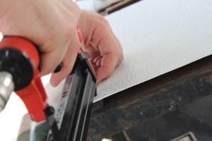 hands using brad nailer on panel