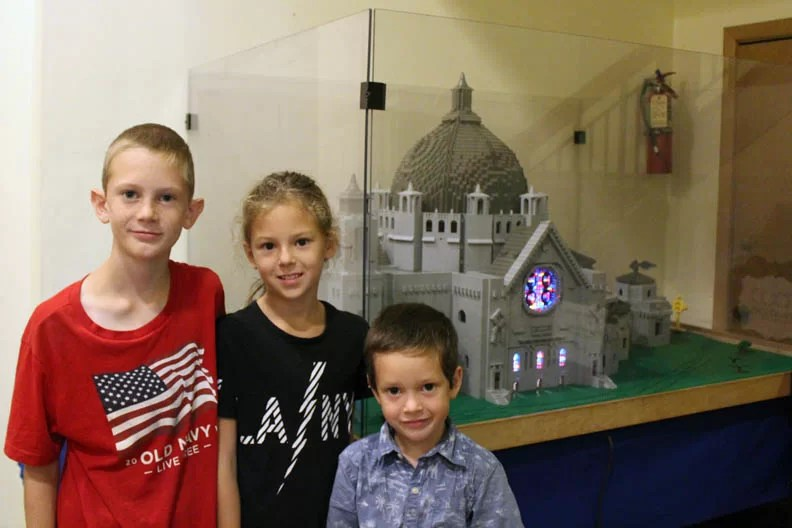 Three kids in front of the Cathedral of Saint Paul lego model